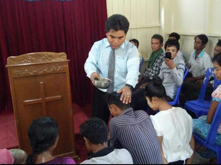 Pastor Naing baptizing new converts at the church in Bogalay, Rakhine