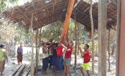 Workers stand up a main support beam at the new house being built for ministry workers
